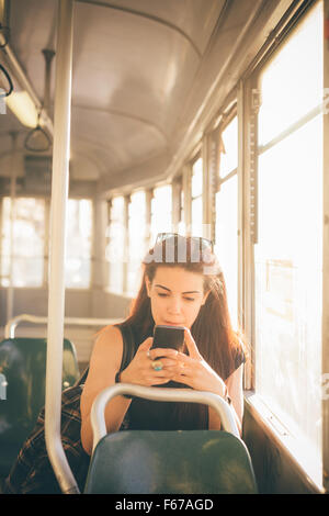 Half length of a young beautiful reddish brown hair caucasian woman using a smartphone on a tram - technology, social - Stock Photo