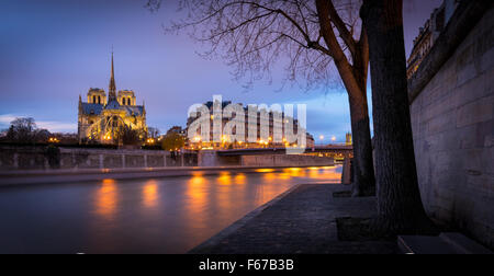 Illuminated Notre Dame de Paris Cathedral at Twilight on Ile de la Cite. Reflection of city lights on the Seine - Stock Photo