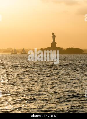 Statue of Liberty before sunset in hazy New York Harbor - Stock Photo