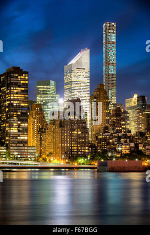 Illuminated Midtown Manhattan skyscrapers and city lights are reflected in East River at twilight. New York City - Stock Photo