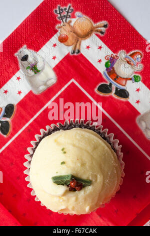 Christmas Pudding Red Velvet muffin on Christmas serviette - Stock Photo