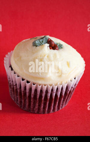 Christmas Pudding Red Velvet muffin isolated on red background - Stock Photo