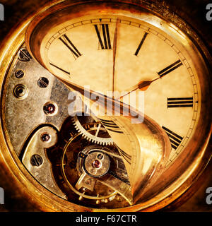 Face of an antique pocket watch being peeled back to reveal the cogs beneath - Stock Photo