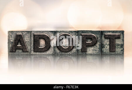 The word 'ADOPT' written in vintage ink stained letterpress type. - Stock Photo