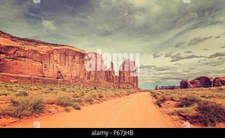 Vintage style photo of sandy road in Monument Valley, Utah, USA. - Stock Photo