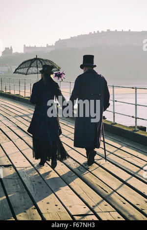 A adult couple dressed in black Victorian period costume walk along the wooden pier at Whitby, during The Goth weekend. - Stock Photo