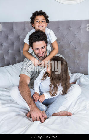 Happy family on bed - Stock Photo