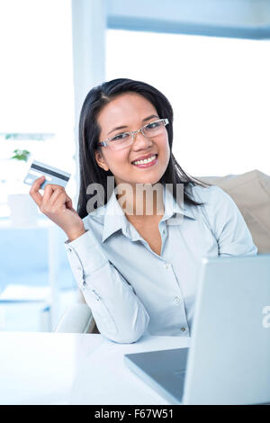 Smiling businesswoman holding credit card - Stock Photo