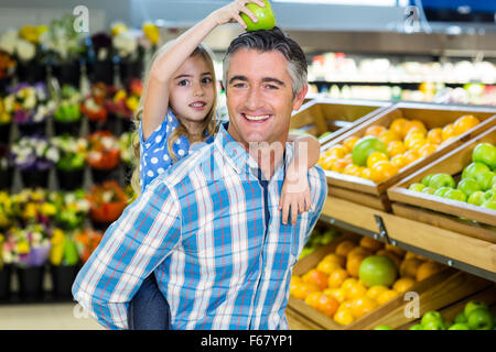Father giving his daughter a piggy back - Stock Photo
