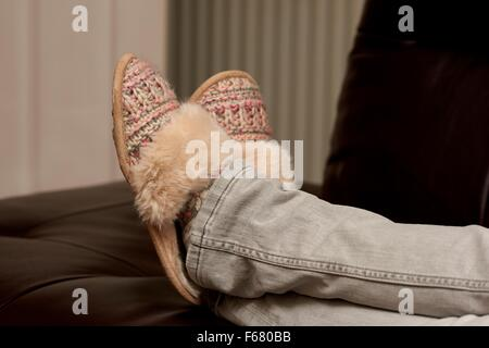 A woman relaxing with her feet up wearing slippers England UK - Stock Photo