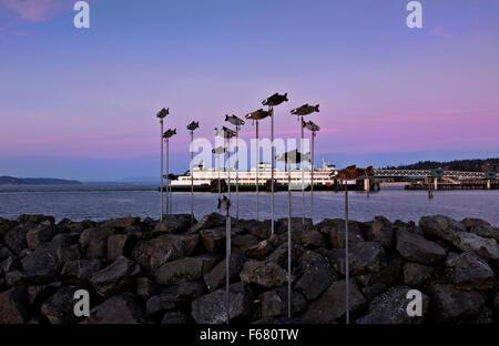 WASHINGTON - Fish sculpture on the Edmonds' fishing pier on the Puget Sound at sunset. The Edmonds-Kingston ferry - Stock Photo