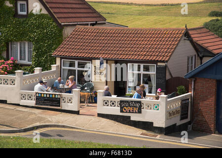 People sitting outside, on the small terrace at The Tea Shop, relaxing & enjoying cups of tea – Staithes, North - Stock Photo