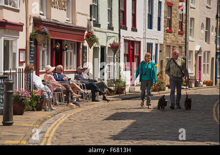 People relaxing, sitting outside a pub or walking along the sunny cobbled High Street - traditional fishing village - Stock Photo