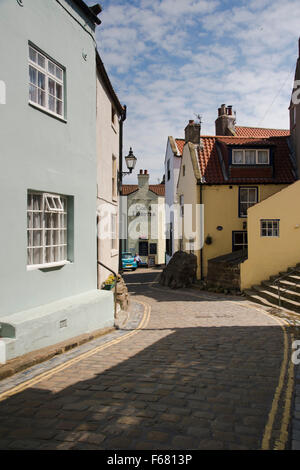 View of quaint cottages on quiet, cobbled High Street in the traditional fishing village of Staithes, North Yorkshire, - Stock Photo
