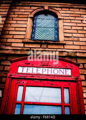 Low angled view of an old telephone kiosk outside Holy Trinity church in Warrington Town centre - Stock Photo