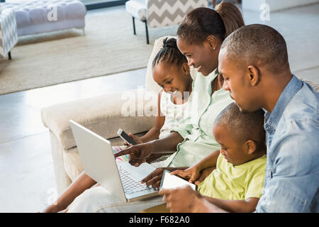 Happy family using technology together - Stock Photo