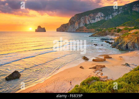 Pan di Zucchero at sunset time, Masua Village Beach, Sardinia Island, Italy - Stock Photo
