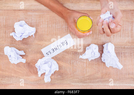 Businesswoman having orange juice and holding crumpled paper - Stock Photo