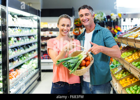 Smiling couple pointing basket with vegetables - Stock Photo