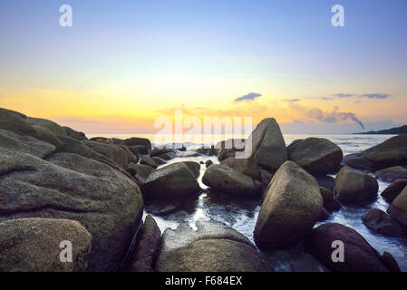sea wave hitting rocks on twilight at famous seaside at Rayong, Thailand - Stock Photo