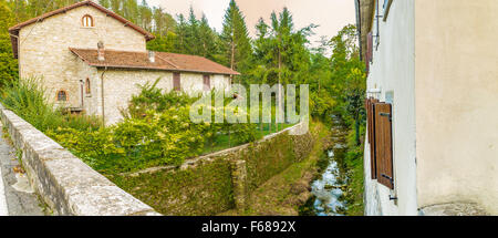 Small stream runs trhough medieval mountain village in Tuscany characterized by houses with walls of stones derived - Stock Photo