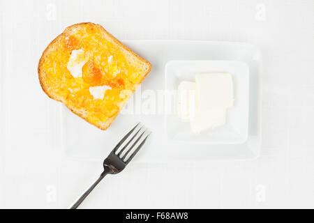 French toast with spread bitter orange marmalade or jam with candied peel, butter curls, fork and dishware on white - Stock Photo