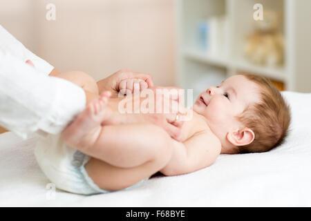 Masseuse or doctor massaging baby boy - Stock Photo