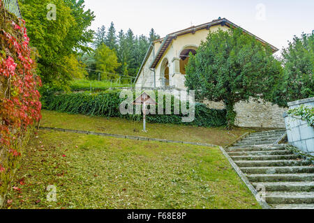 wooden cross near boston ivy in the garden in front of the church in a medieval mountain village in Tuscany - Stock Photo