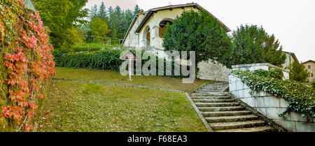 wooden cross in the garden in front of the church near a creeper and a staircase in a medieval mountain village - Stock Photo