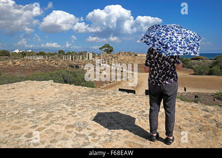 Rear view of a mature senior woman tourist shading herself from hot sun at the Roman ruins of Salamis near Famagusta - Stock Photo
