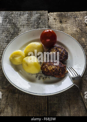 Nov. 1, 2015 - Homemade burgers, boiled potatoes and pickled tomatoes on old weathering background (Credit Image: - Stock Photo