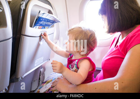 Mother travelling with one year old baby on an aeroplane - Stock Photo