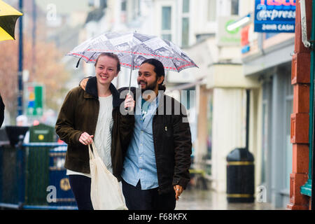 Aberystwyth Wales UK, Saturday 14 November 2015  A young couple smile as they walk under an umbrella to avoid getting - Stock Photo