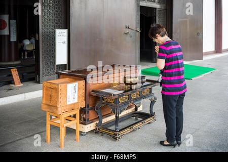 Woman praying at Zojo Ji Shrine in Tokyo, Japan - Stock Photo