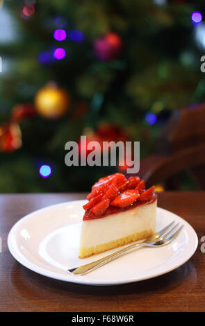 Fresh strawberry cheesecake. Selective Focus on the front upper edge of cake. Christmas tree in background - Stock Photo
