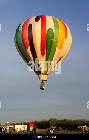 A single balloon floats over the field below - Stock Photo