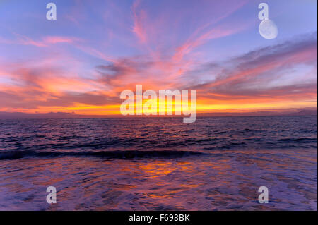 Ocean sunet moon is a colorful cloud filled sky over the ocean with a three quarter moon rising high in the sky. - Stock Photo