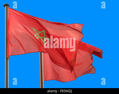 Two Morocco flags waving in the blue sky, copy space on the right side - Stock Photo