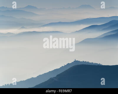 series of mountain's and hill's profiles surrounded by evening autumn mist in liguria Italy - Stock Photo