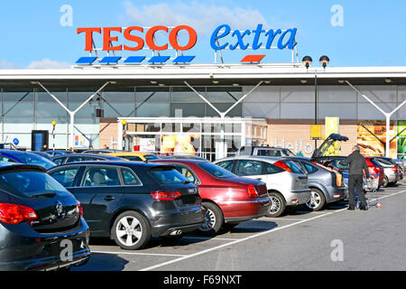 Supermarket Tesco Extra car park shopper loading trolley contents into car boot at East London store obscured number - Stock Photo