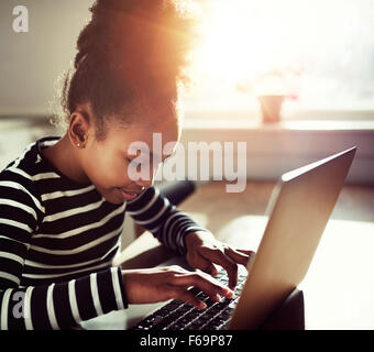 young black girl with a fun afro topknot concentrating as she types on a laptop computer, close up side view with - Stock Photo