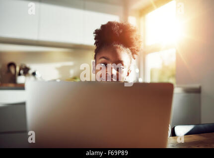 Smiling black girl with a cute hairstyle sitting at a laptop computer browsing the internet and her social media - Stock Photo