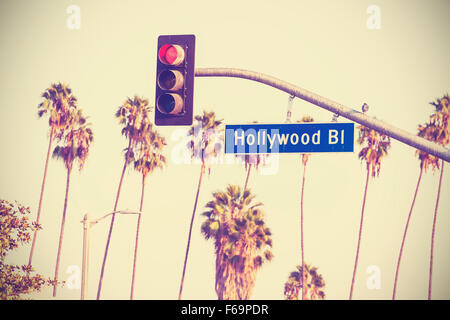 Vintage retro toned Hollywood boulevard sign and traffic lights with palm trees in the background, Los Angeles, - Stock Photo