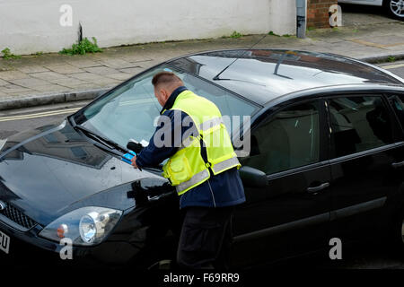 traffic warden issuing a parking ticket for a violation england uk - Stock Photo