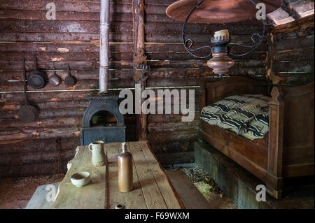 Rustic log cabin interior with wooden furniture - Stock Photo