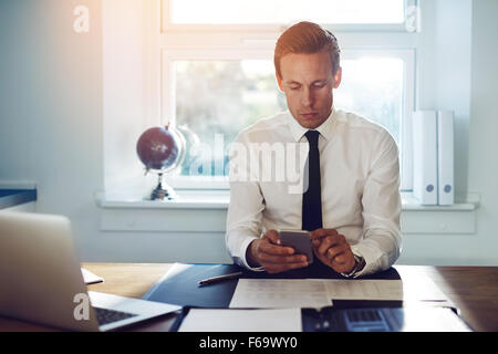 Executive business man texting on his phone and checking mail while sitting at his desk at the office - Stock Photo