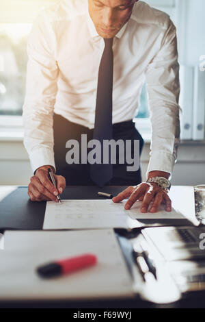 Business man closing a deal signing documents at desk in office wearing white shirt and tie - Stock Photo