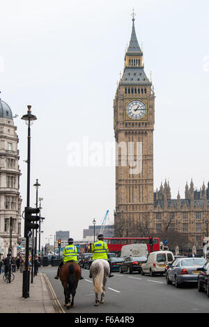 Two unidentified mounted police officers ride their horses in front of Big Ben on April 13, 2007 in London, UK. - Stock Photo