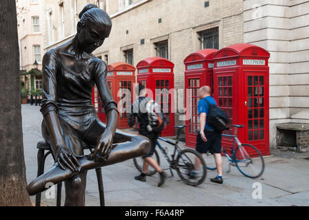 Two men walk in a street, passing by four red telephone boxes and a statue on April 8, 2007 in Covent Garden, London, - Stock Photo
