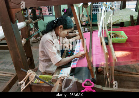 Two women weaving on a horizontal loom using shuttles with thread spools. Partially woven silk fabric visible. Mandalay, - Stock Photo